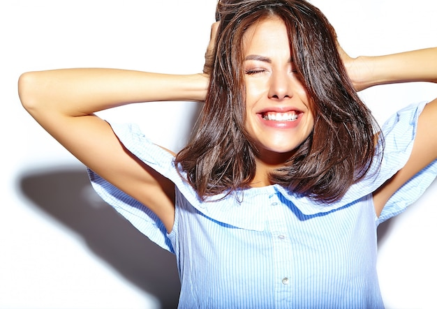 Portret wesoły uśmiechający się moda kobieta wariuje w codzienne niebieskie hipster letnie ubrania bez makijażu na białej ścianie