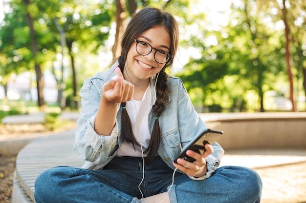 Portret wesoły uśmiechający się śliczna młoda studentka w okularach, siedząca na ławce na świeżym powietrzu w parku przyrody przy użyciu telefonu komórkowego na czacie słuchania muzyki przez słuchawki.