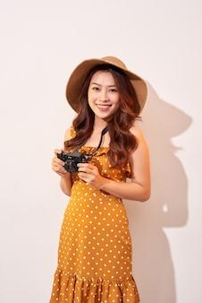 Portret wesoły uśmiechnięta młoda kobieta robienie zdjęć z inspiracją i na sobie letnią sukienkę. dziewczyna trzyma aparat retro. model pozuje na beżowej ścianie w kapeluszu