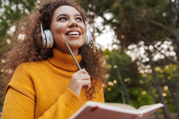 Portret wesoły zadowolony piękna młoda kobieta kędzierzawy siedzieć na ławce w parku na zewnątrz, słuchając muzyki w słuchawkach, pisząc notatki w notesie.