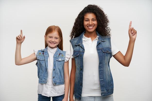 Portret wesołych, ładnych młodych dziewcząt z długimi włosami unoszącymi palce wskazujące i patrzącymi radośnie z szerokimi uśmiechami, odizolowany na białym tle w zwykłych ubraniach
