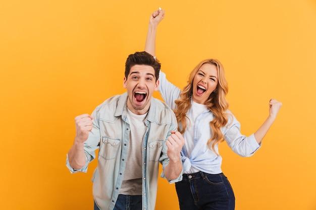 Portret wesołych ludzi, mężczyzny i kobiety w podstawowym ubraniu, uśmiechniętych i zaciśniętych pięściami jak zwycięzcy lub szczęśliwi ludzie, odizolowani na żółtej ścianie
