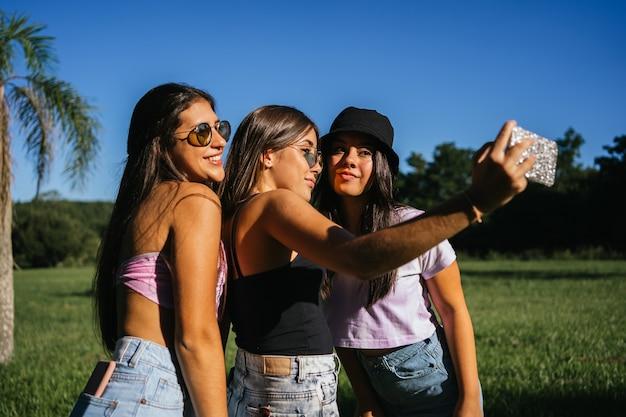 Portret wesołych nastoletnich przyjaciół biorąc selfie.