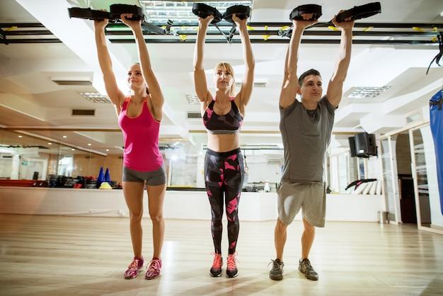 Portret widok pięknej, zdrowej sylwetki aktywnej sportowej grupy fitness stojącej i rozciągającej się z trx na suficie w siłowni.
