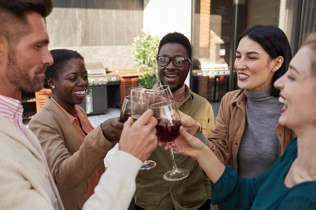 Portret wieloetnicznej grupy przyjaciół, brzęczących kieliszkami, delektując się winem podczas imprezy na świeżym powietrzu na tarasie