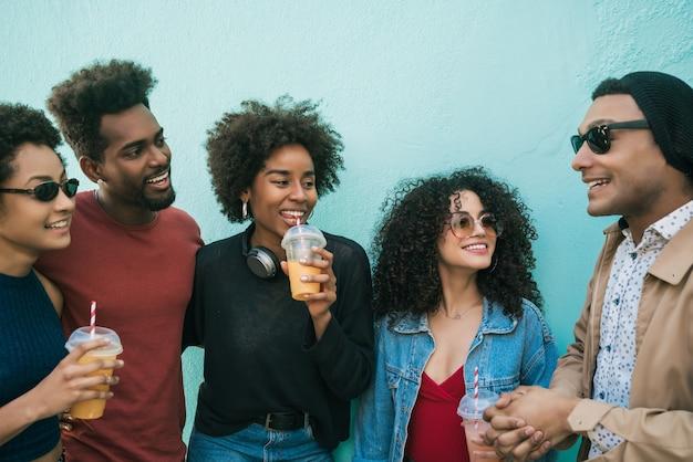 Portret wieloetnicznej grupy przyjaciół, którzy razem bawią się i cieszą się dobrym czasem przy piciu świeżych soków owocowych.