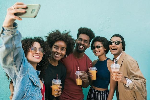 Portret wieloetnicznej grupy przyjaciół, wspólnej zabawy i robienia selfie przy piciu świeżego soku owocowego.