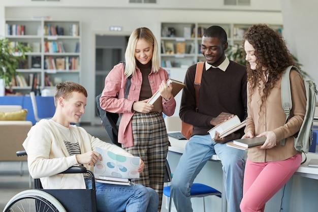 Portret wieloetnicznej grupy studentów w bibliotece uczelni z chłopcem na wózku inwalidzkim na pierwszym planie