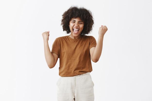 Portret wiwatującej beztroskiej i szczęśliwej triumfującej afroamerykańskiej nastolatki z fryzurą afro podnoszącą pięści w zwycięstwie lub wygrywający gest uśmiechnięty szeroko z dźwiękiem tak