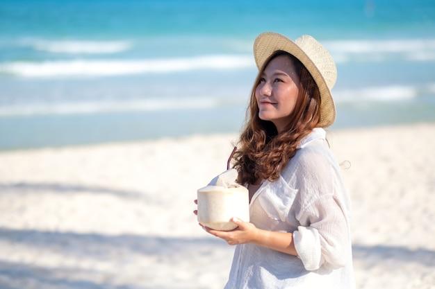 Portret wizerunek pięknej kobiety azjatyckie gospodarstwa i picia soku kokosowego na plaży
