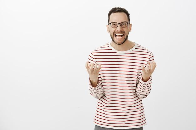 Portret wkurzonego, przygnębionego europejskiego dorosłego chłopaka w okularach, krzyczącego głośno i zaciskającego pięści, wściekłego i wściekłego podczas walki z żoną, chcącego się rozwieść na szarej ścianie