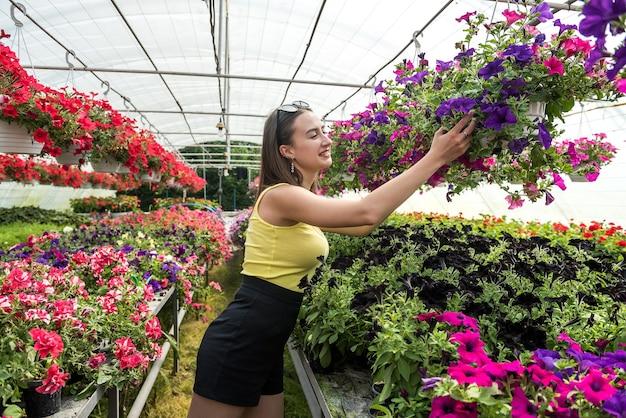 Portret właściciel szklarni szczęśliwa kobieta pozuje między jej kwiatami. szczęśliwa kwiaciarnia w szklarni