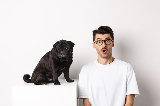 Portret właściciela psa i małego słodkiego mopsa wpatrującego się w aparat zaskoczony i zdumiony, stojący na białym tle