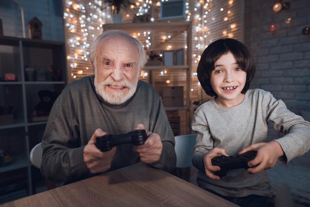 Portret wnuk zagraj w grę wideo z dziadkiem