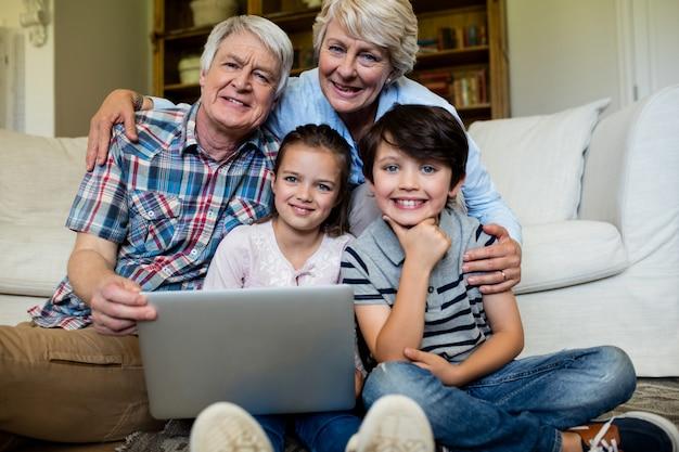 Portret wnuków i dziadków z laptopem w salonie