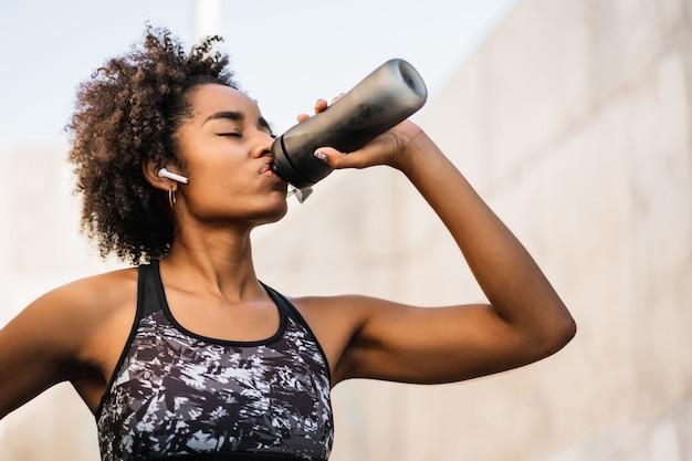 Portret wody pitnej sportowiec kobieta po treningu na świeżym powietrzu.