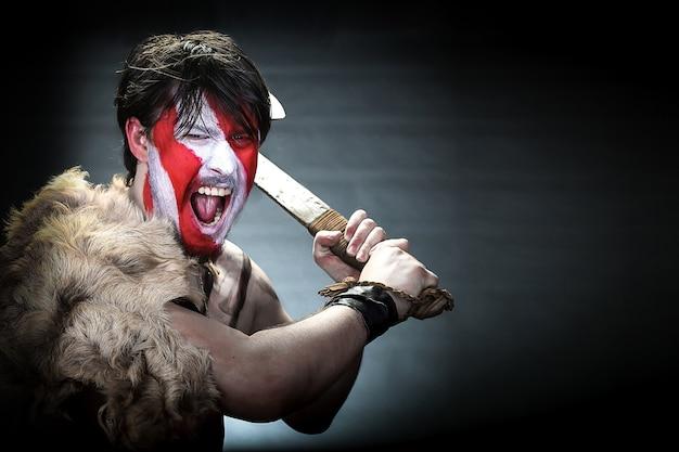 Portret wojownika wymachującego toporem, wściekle wrzeszczącego