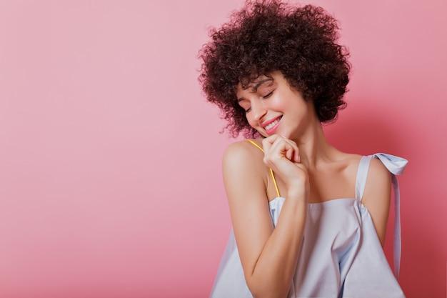 Portret wrażliwej krótkowłosej z lokami kobieta ubrana w błękitną bluzkę pozuje z czarującym uśmiechem na różowo