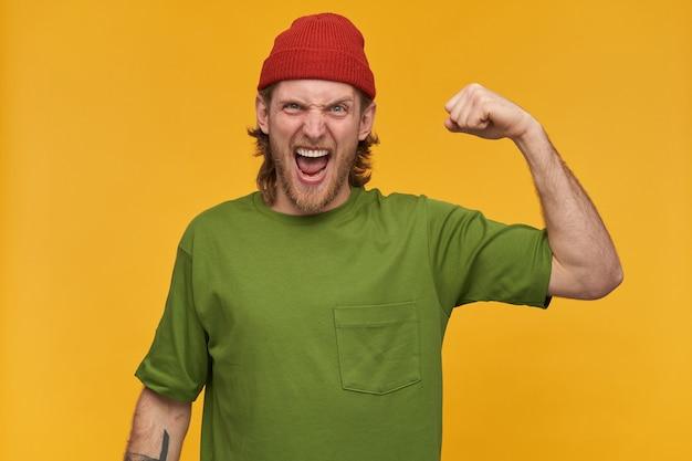 Portret wściekłego, energicznego mężczyzny z blond fryzurą i brodą. ubrana w zieloną koszulkę i czerwoną czapkę. ma tatuaż. pokazuje swoje bicepsy. ma moc. pojedynczo na żółtej ścianie