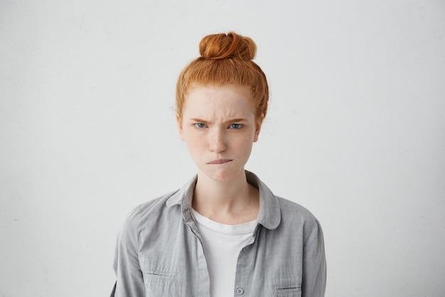 Portret wściekłego, marszczącego brwi, nastolatka o imbirowej bułce gryzącej wargę ze złością na białym tle. młoda, piegowata ruda kobieta o niezadowolonym wyrazie twarzy