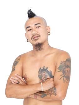 Portret wściekłego, szalonego azjatyckiego faceta punkowego z fryzurą irokezem, piercingiem i tatuażem na białym tle