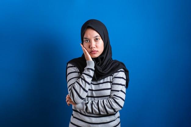 Portret wściekłej cynicznej azjatyckiej muzułmańskiej kobiety z podejrzanym wyrazem twarzy patrzącej na kamerę, nieufna koncepcja błędnych wątpliwości