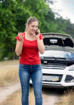 Portret wściekłej młodej kobiety stojącej przy zepsutym samochodzie i rozmawiającej przez telefon komórkowy