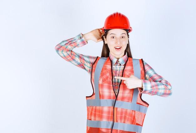 Portret wskazuje na białym tle pracownik budowlany kobieta.