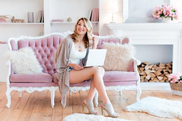 Portret wspaniała blondynki kobieta z laptopem pracuje w domu.