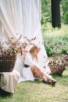 Portret wspaniała kobieta przy ogródem z biel ściany obsiadaniem na trawie i główkowaniem w biel sukni podczas dnia.