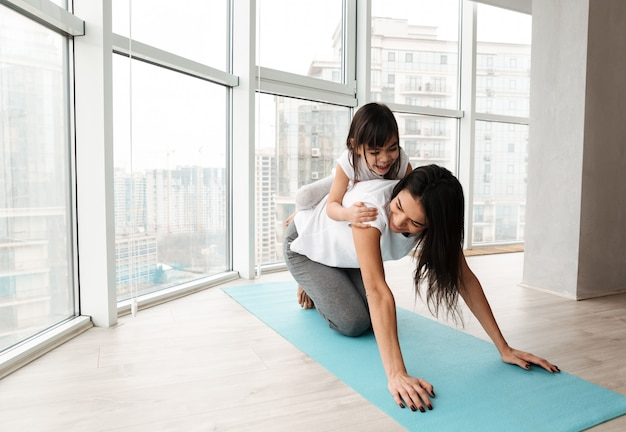 Portret wspaniała rodziny matka, dziecko ma zabawę i, podczas gdy robić sprawności fizycznych ćwiczeniom na joga macie w domu