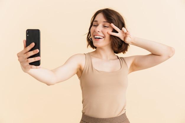 Portret wspaniałej kaukaskiej kobiety w wieku 20 lat ubranej w zwykłe ubrania pokazujące znak pokoju podczas robienia zdjęcia selfie na telefonie komórkowym na białym tle