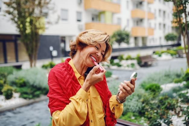 Portret wspaniały kaukaski blondynka starszy kobieta trzymając lustro i kładąc szminkę