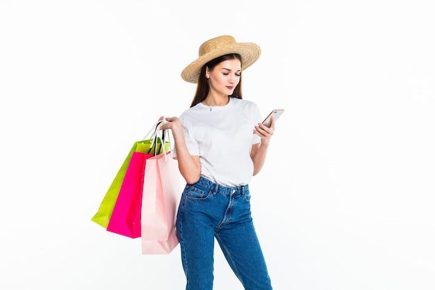 Portret wspaniały kobieta zakupy używać jej smartphone odizolowywającego na biel ścianie