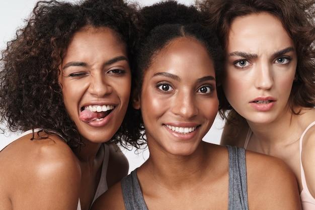 Portret wspaniałych wielorasowych kobiet stojących razem i patrzących na kamerę