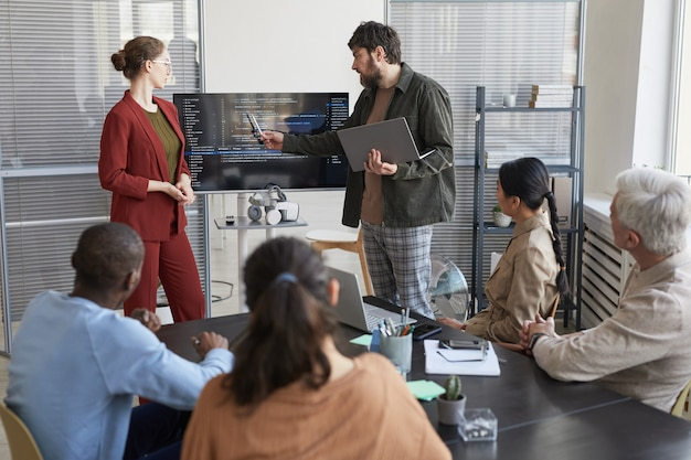 Portret współczesnego brodatego biznesmena przedstawiającego prezentację w biurze zespołowi it i wskazującego na kod na ekranie, kopia przestrzeń
