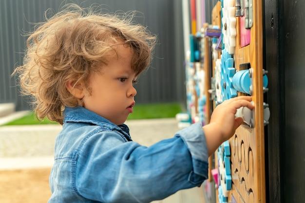 Portret współczesnego małego chłopca bawiącego się z deską zajęty na zewnątrz na publicznym placu zabaw.