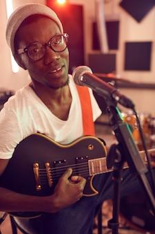 Portret współczesnego mężczyzny afroamerykańskiego śpiewającego do mikrofonu