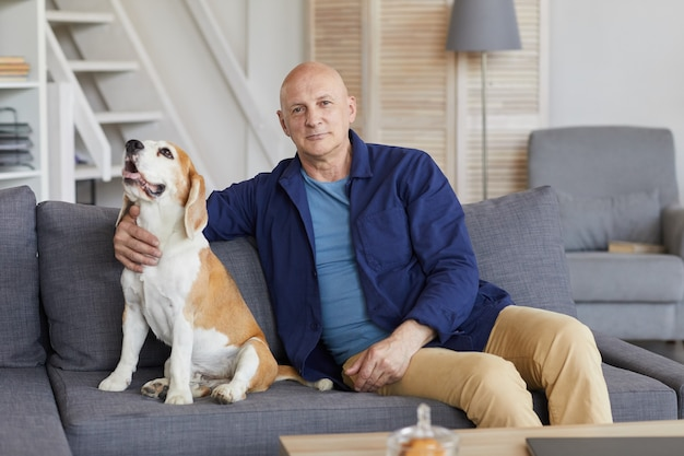 Portret współczesnego starszego mężczyzny z psem siedząc na kanapie, pozowanie we wnętrzu domu