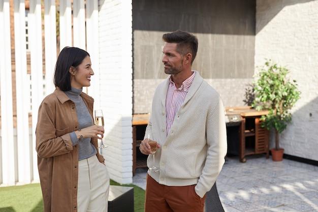 Portret współczesnej dorosłej pary rozmawiającej w pasie, stojącej na tarasie z kieliszkami do szampana,