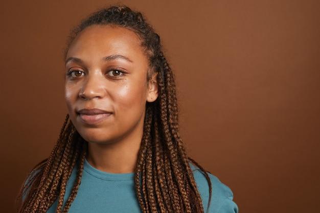 Portret współczesnej kobiety african-american uśmiechnięta pozowanie na brązowo
