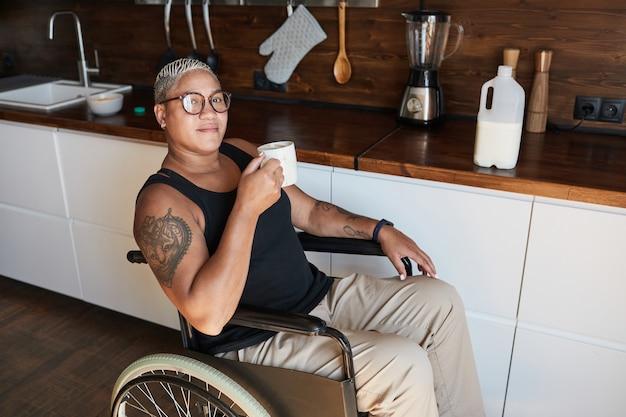 Portret współczesnej wytatuowanej kobiety na wózku inwalidzkim, cieszącej się kawą w domu i patrzącej w kamerę, kopia przestrzeń