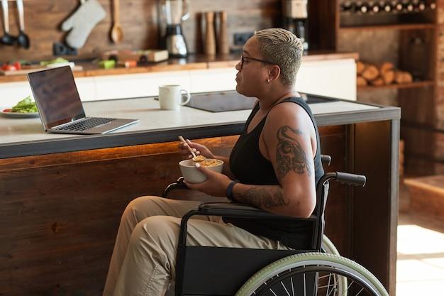 Portret współczesnej wytatuowanej kobiety na wózku inwalidzkim, oglądającej filmy na laptopie w domu, kopia przestrzeń