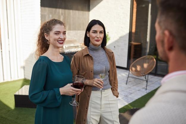 Portret współczesnych dorosłych kobiet rozmawiających z przyjaciółmi i uśmiechających się, stojąc na tarasie podczas imprezy,