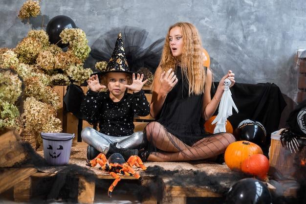Portret, wśród dekoracji na święta halloween, dwie dziewczynki bawią się dynią na tle czarno-pomarańczowych dekoracji