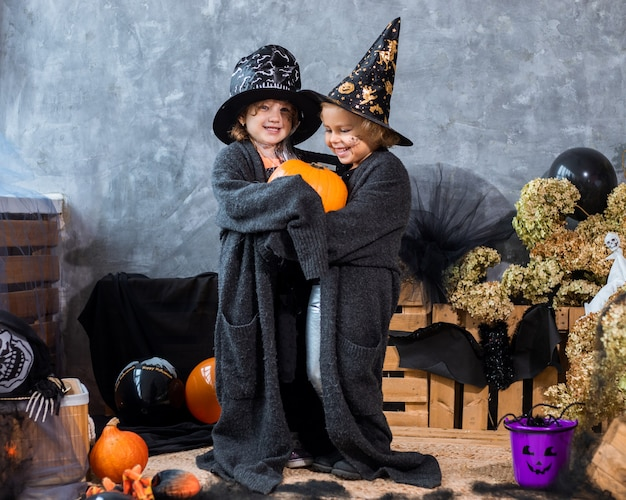 Portret, wśród dekoracji na święta halloween, dwie dziewczynki w wieku 4-5 lat bawią się dynią na tle czarno-pomarańczowych dekoracji