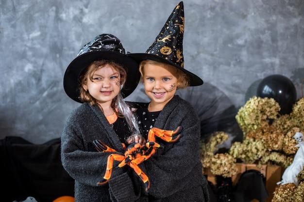 Portret, wśród dekoracji na święta halloween, dwie dziewczynki w wieku 4-5 lat bawią się pająkiem na tle czarno-pomarańczowych dekoracji