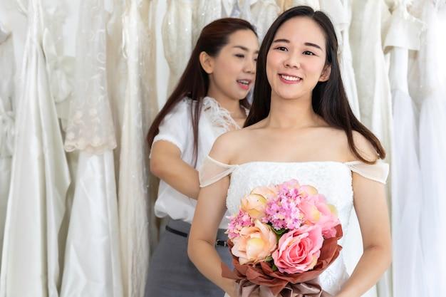 Portret wybiera suknię w sklepie z krawieckim asystentem azjatycka kobieta.