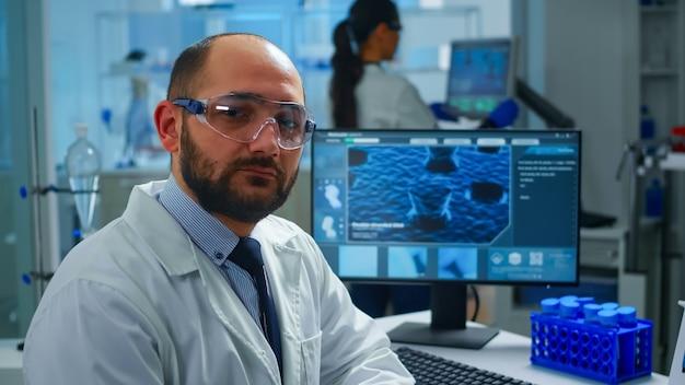 Portret wyczerpany naukowiec mężczyzna patrząc na kamery siedząc przed komputerem z obrazem skanowania dna. chemik badający ewolucję wirusów przy użyciu zaawansowanych technologicznie i chemicznych narzędzi do badań naukowych