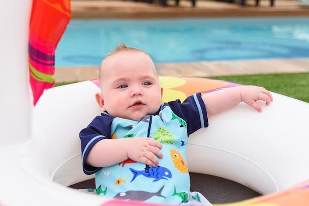 Portret wygodnego chłopca w pływaku w pobliżu letniego basenu